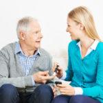 Frau misst Blutzucker bei einem Senioren