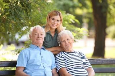 Woman with elderly parents in park on sunny day