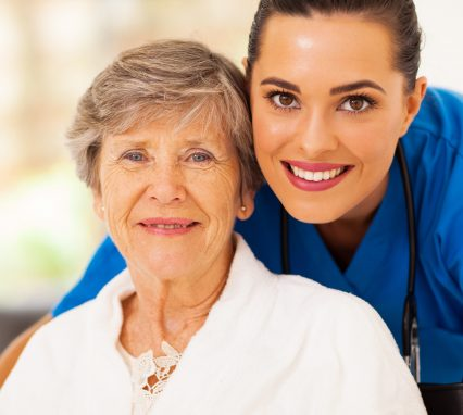 happy senior woman on wheelchair with caregiver