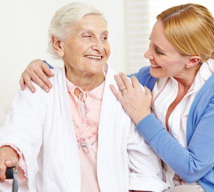 Lachende Seniorin zu Hause schaut ihre Tochter an