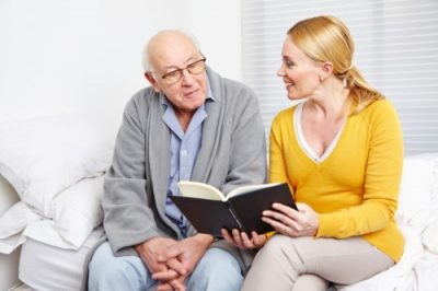 Frau liest einem alten Mann im Seniorenheim ein Buch vor