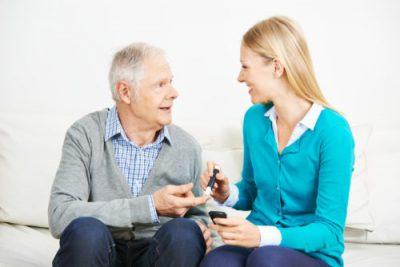 Junge Frau misst Blutzucker bei einem Senioren mit Diabetes im Seniorenheim